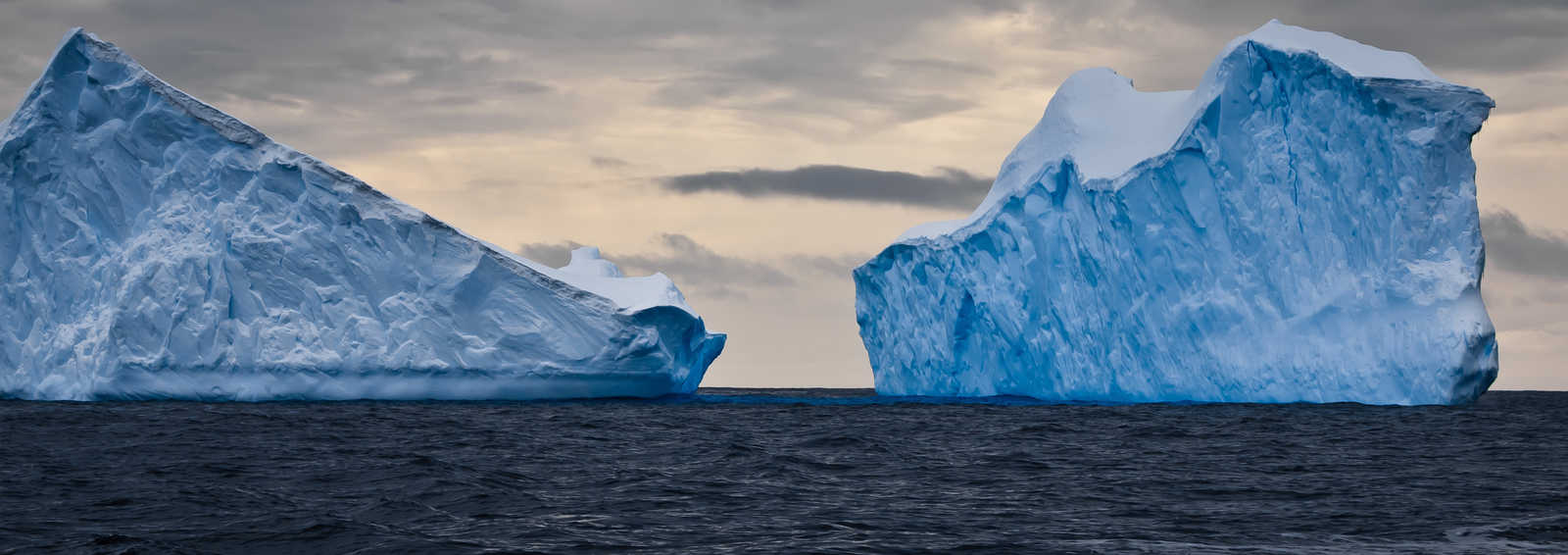 Huge icebergs in Antarctica, dark sky