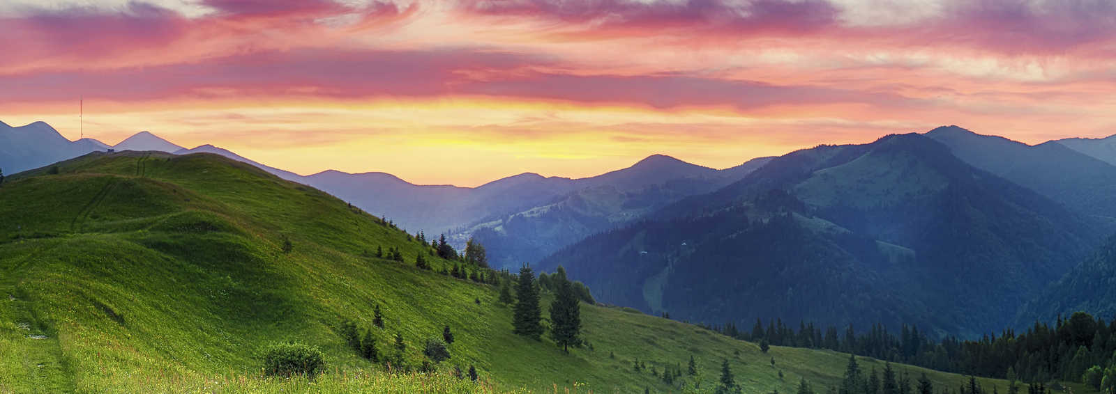 Carpathian mountains summer sunset landscape with dramatic sky and blue mountains