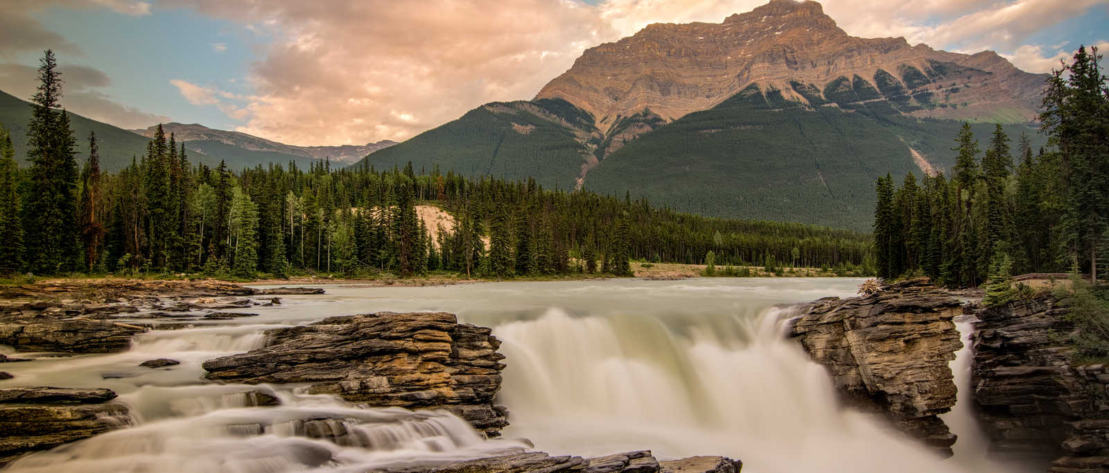Long exposure of the beautiful Athabasca Falls with towering sunlit of Mount Kerkeslin in the background, Canada.